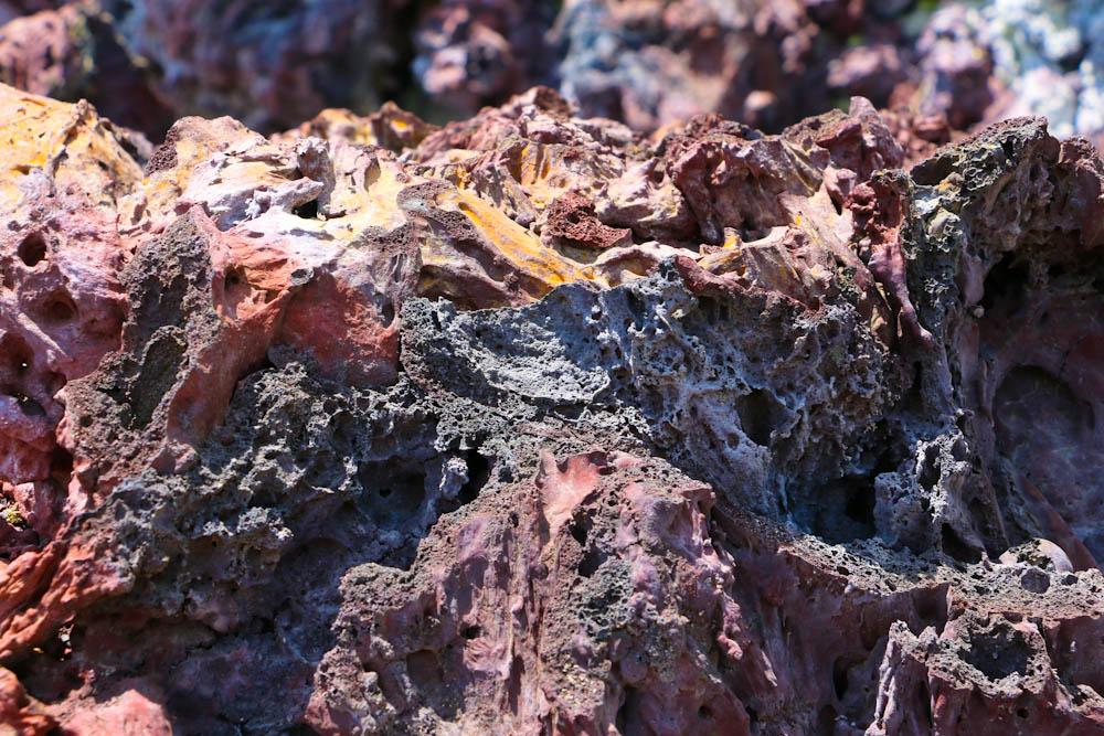 Verschieden farbige Gesteinsschichten leuchten in der Mittagssonne.